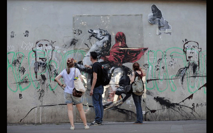 People look at a recent artwork by anonymous street artist Banksy in Paris, on June 28, 2018. Picture: AFP.