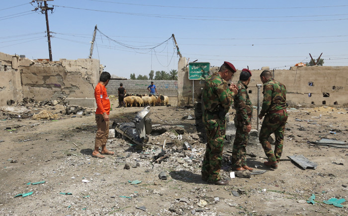 FILE: Iraqi security forces stand at the site of a car bomb attack that targeted Shiite pilgrims in Baghdad's Nahrawan area on 30 April, 2016. Picture: AFP.