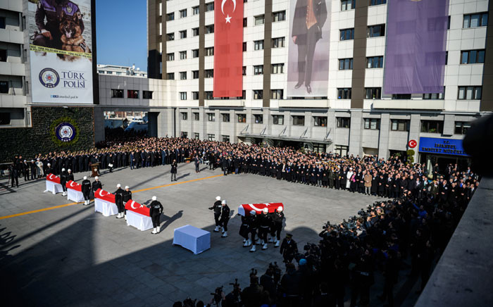 Turkish police officers stand to attention next to the coffins of their comrades as others parade with a coffin during a funeral ceremony at Istanbul's police headquarters on December 11, 2016, a day after twin bombings. Picture:  AFP.