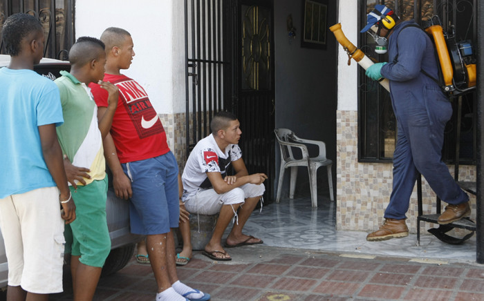 """Residents wait outside as health workers fumigate their homes in Cali, Colombia, as a precaution against the mosquito 'Aedes aegypti', which spreads the Zika, Dengue and Chikunguna viruses. Picture: EPA/Christian Escobar Mora."""""""