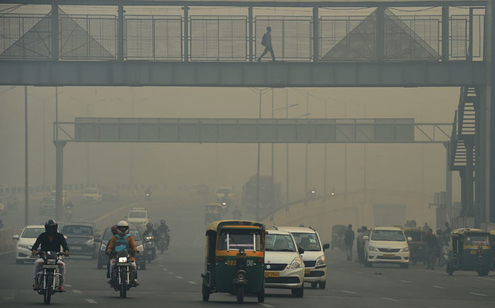 FILE: Motorists are seen along a busy road amid heavy smog in New Delhi. Picture: AFP