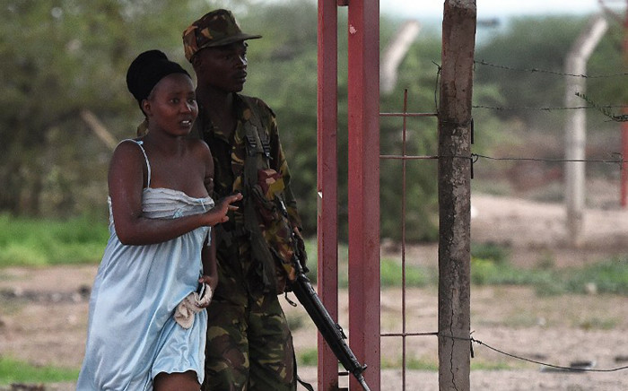 A member of the security forces escorts a student out of Garissa University campus in Garissa on 2 April, 2015, after an attack by Somalia's Al-Qaeda-linked Shebaab gunmen. Picture: AFP