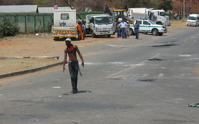 University of Limpopo student stands in the middle of the road during the Fess Must Fall protests. Picture: Pelane Phakgadi/EWN.