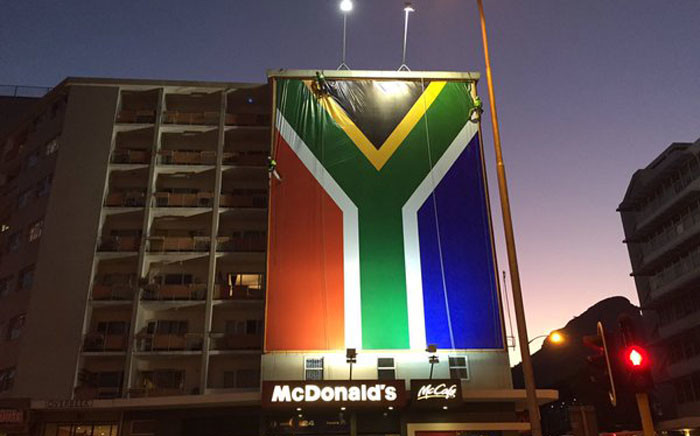The SA flag now hangs in the prime ad space once home to the #ZumaMustFallBillboard. Workers busy adjusting edges. Picture: Natalie Malgas/EWN.