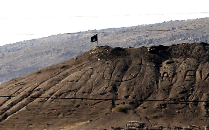 FILE: An Islamic State flag flies on a hill overlooking the Syrian town of Kobani, as seen from the border with Turkey in Suruc district, near Sanliurfa, Turkey, 07 October 2014. Picture: EPA.