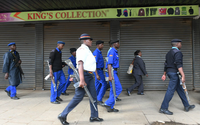 Kenyan policemen patrol along a deserted street before the beginning of a curfew which was ordered by Kenyan President, Uhuru Kenyatta, to contain the spread of the COVID-19 coronavirus on 27 March 2020 in Nairobi. Picture: AFP