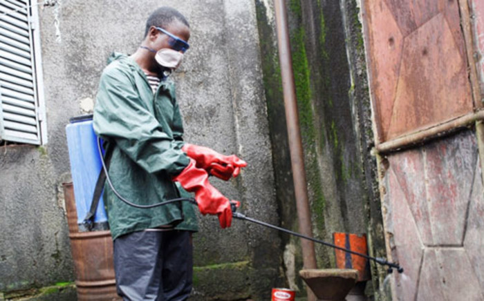A local volunteer with NGO Action against Hunger sprays disinfectant at a home where three people were infected with cholera. Dabondy neighbourhood of the Guinean capital Conakry. Picture: Irin news.