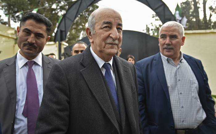 Algerian presidential candidate Abdelmadjid Tebboune (C) arrives to cast his ballot in the capital Algiers on 12 December 2019. Picture: AFP