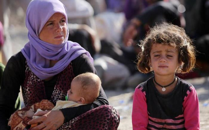 FILE: A Yazidi Iraqi woman sits with her children at the Bajid Kandala camp near the Tigris River, in Kurdistan's western Dohuk province, where they took refuge after fleeing advances by Islamic State jihadists in Iraq in 2014. Picture: AFP.