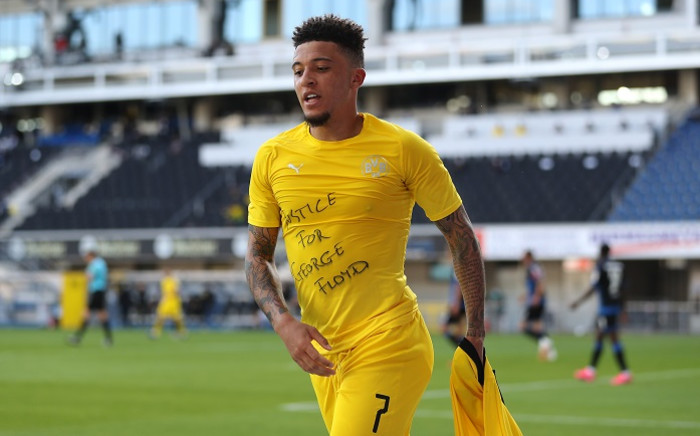 Dortmund's English midfielder Jadon Sancho shows a 'Justice for George Floyd' shirt as he celebrates after scoring his team's second goal during the German first division Bundesliga football match SC Paderborn 07 and Borussia Dortmund at Benteler Arena in Paderborn on 31 May 2020. Picture: AFP.