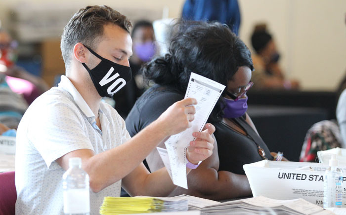 Fulton County election workers examine ballots while vote counting, at State Farm Arena on 5 November 2020, in Atlanta, Georgia. Picture: AFP
