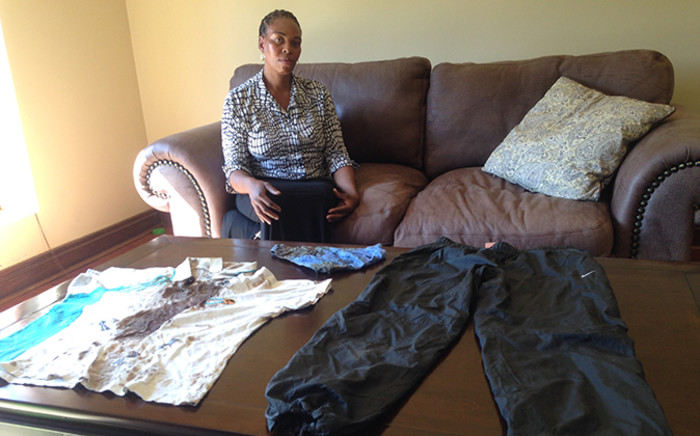William Sithole's mother Lindiwe  looks on as her murdered son's bloodied clothes lie on the table. Picture: Vumani Mkhize/EWN.