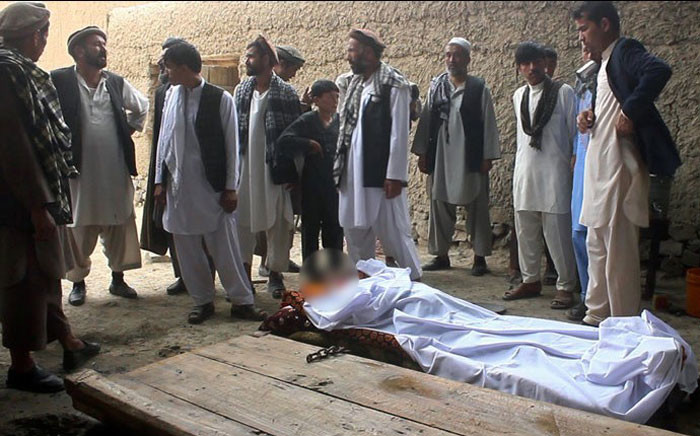 Afghan residents and relatives stands over the bodies of victims after a gunfight broke out at a wedding party at Deh Salah district of Baghlan Province on 27 July 2015. Picture: AFP.