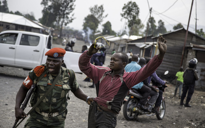 A man is arrested by a member of the military police after people attempted to block the road with rocks, in the neighbourhood of Majengo in Goma, eastern Democratic Republic of the Congo, on 19 December 2016, as tensions rose with one day left of Congolese President Joseph Kabila's mandate. Picture: AFP.
