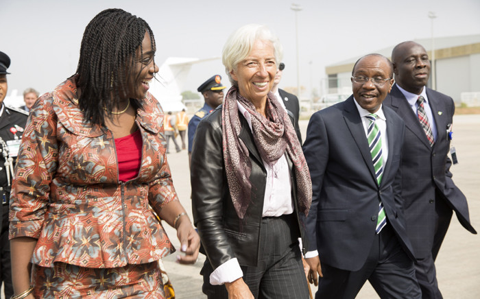 International Monetary Fund Managing Director Christine Lagarde (C), accompanied by Nigerias Finance Minister Kemi Adeosun (L) and Nigerias Central Bank Governor Godwin Emefiele, at the Nnamdi Azikiwe International Airport on 4 January, 2016 in Abuja. Picture: AFP.
