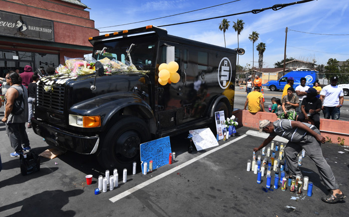 FILE: Fans pay their respects beside an armored vehicle that belonged to, Grammy-nominated rapper Nipsey Hussle, at a makeshift memorial outside The Marathon clothing store where he was fatally shot in Los Angeles, California on 1 April 2019. The Grammy-nominated rapper found minor commercial success but was highly revered among his peers, and his shock death triggered an outpouring of tributes from hip hop royalty. Picture: AFP