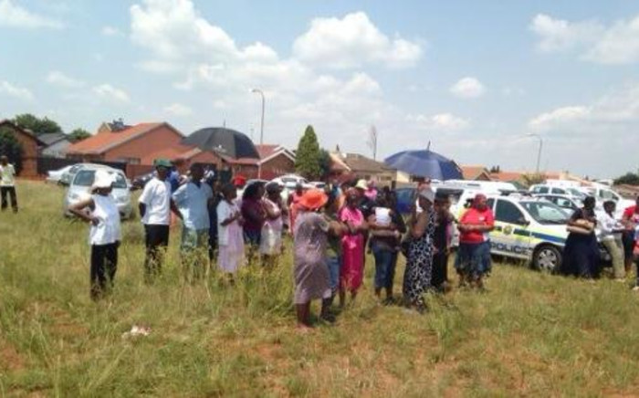 Shocked residents near where the bodies of two teenage girls were discovered on 19 February 2014, in Dobsonville, Soweto. Picture: Masego Rahlaga/EWN.