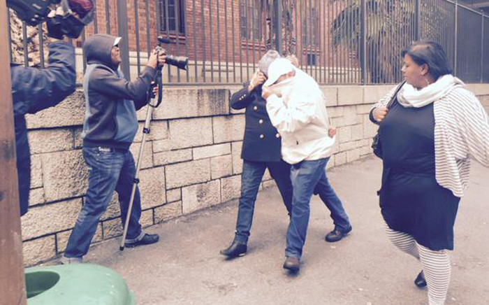 The Lavender Hill woman accused of snatching Zephany Nurse at Groote Schuur Hospital in 1997 covers her face as she leaves court on 24 July 2015. Picture: Giovanna Gerbi/EWN.