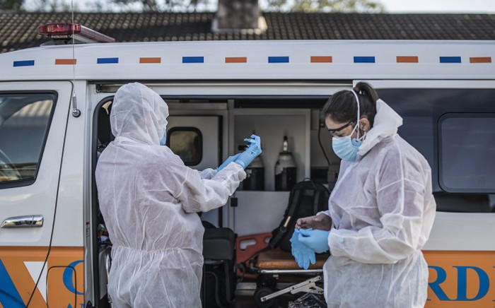A crew of a private ambulance service in Port Elizabeth wear personal protective equipment on 11 July 2020 ahead of checking on a patient affected by COVID-19 coronavirus at her home. Picture: AFP.