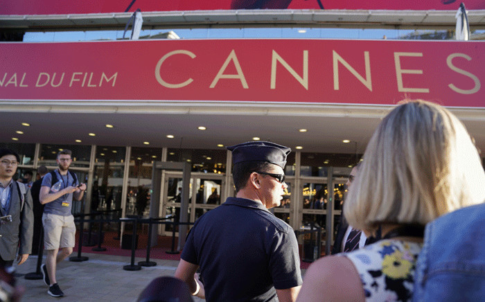 FILE: A Police officers stands guard as people wait outside the main entrance of the Festival's Palace on 20 May 2017 after it was evacuated over a suspicious package, at the 70th edition of the Cannes Film Festival in Cannes, southern France. Picture: AFP.