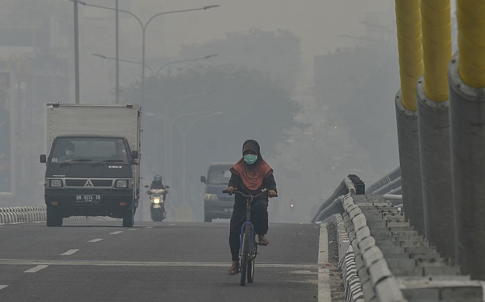 A cyclist makes her way across a bridge amid choking smog due to forest fires in Pekanbaru, Riau on 19 September 2019. Picture: AFP