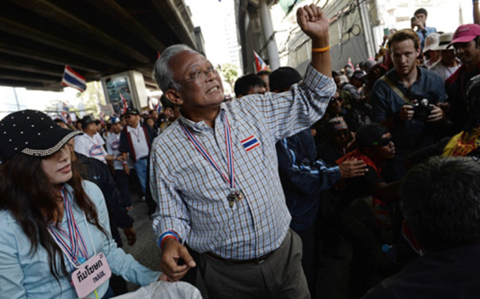 Thai protest leader Suthep Thaugsuban greets supporters as anti-government protesters march through downtown Bangkok on 15 January, 2014. Picture: AFP.