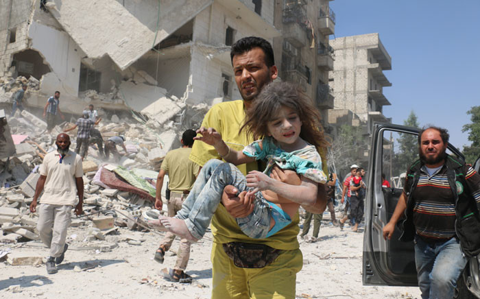 FILE: A Syrian man carries a child in a district of Aleppo after an air raid. Picture: AFP.