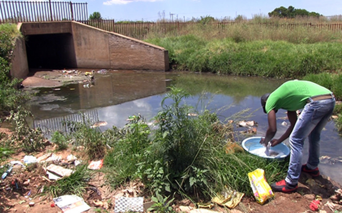 A young man washing his clothes in a sewage filled stream in Protea South in Soweto. Picture: Reinart Toerien/EWN.