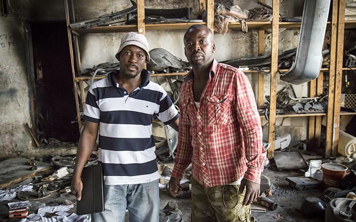 Razak and his brother Daniel Agbenoza stand in their burnt out workshop, after looters broke in, stealing valuables, and setting fire to the building. Picture: Thomas Holder/EWN