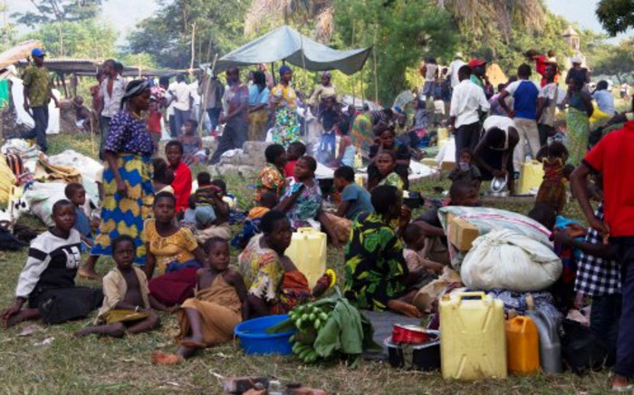 FILE: Refugees from eastern Democratic Republic of Congo (DRC) wait on 13 July 2013 at the Busunga border in western Uganda. More than 30,000 refugees from the eastern DRC have crossed the border into western Uganda's Bundibugyo district after rebels from a Ugandan-led rebel group, the Allied Democratic Forces, attacked the town of Kamango in the northernmost part of North Kivu province. Picture: AFP