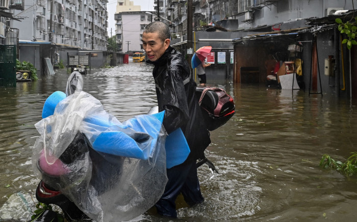 A man pushes a scooter while wading in a flooded street in a neighborhood in Ningbo, eastern China's Zhejiang province on 25 July 2021, as Typhoon In-Fa lashes the eastern coast of China. Picture: Hector RETAMAL / AFP