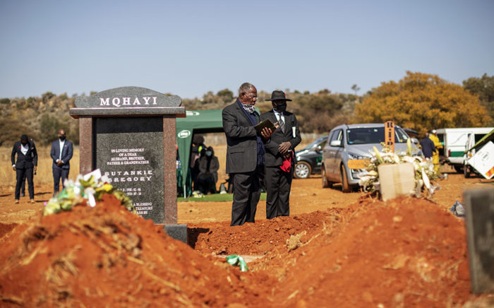 FILE: A pastor reads a passage from the Bible during the funeral of Modise Motlhabane, who died of COVID-19 coronavirus, at the Westpark cemetery in Johannesburg, on 22 July 2020. Picture: AFP