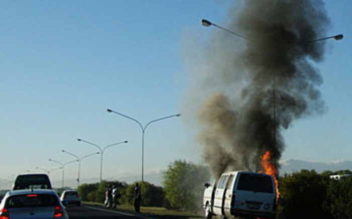 A taxi burns on the side of the N2 highway in Cape Town, on April 11, 2012. Picture:Grant Hillebrand/iWitness