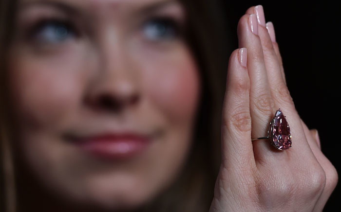 A woman poses for a photograph holding a vivid pink pear-shaped 15.38 carat diamond, known as the Unique Pink,' during a press preview at Sothebys auctioneers in London, on 7 April, 2016. The diamond is expected realise 19-26 million pounds ($28-38 million dollars) at auction in Geneva on 17 May, 2016. Picture: AFP