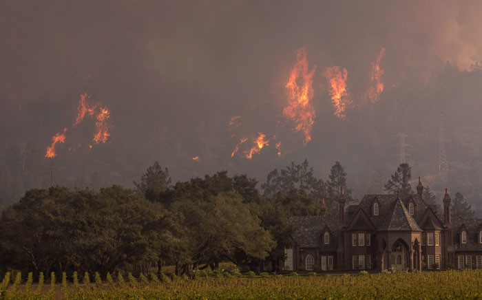 Flames rise behind Ledson Winery on October 14, 2017 in Kenwood, near Santa Rosa, California. Picture: AFP.