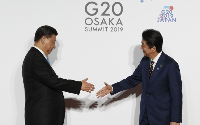 FILE: China's President Xi Jinping (L) is welcomed by Japanese Prime Minister Shinzo Abe upon his arrival for a welcome and family photo session at the G20 Summit in Osaka on 28 June 2019. Picture: AFP