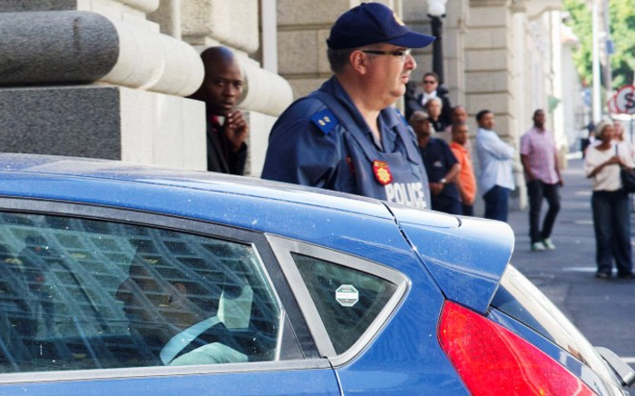 British businessman Shrien Dewani (L) sits in a car driven into the Western Cape High Court, on 8 December, 2014, in Cape Town. Picture: AFP.