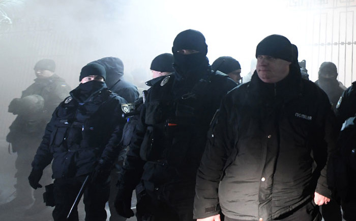 Police officers stand in front of the Russian Embassy in Kiev late on 25 November, 2018, while smoke from a flare thrown by protesters is seen during a rally following an incident in the Black Sea off Moscow-annexed Crimea, in which three Ukrainian naval vessels were seized by a Russian border guard vessel, as the three ships were on their way through the Kerch Strait heading for the port of Mariupol. Picture: AFP