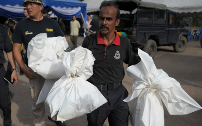 A Malaysian policeman carries human skeletal remains inside plastic bags exhumed from graves near the Malaysia/Thailand border in Wang Kelian on 25 May, 2015. Picture: AFP.