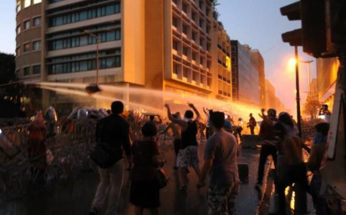 "Lebanese protesters chant slogans as riot police fire water cannons following a demonstration, organised by ""You Stink"" campaign, to protest against the ongoing country's trash crisis on 23 August, 2015 in the capital Beirut. Picture: AFP."