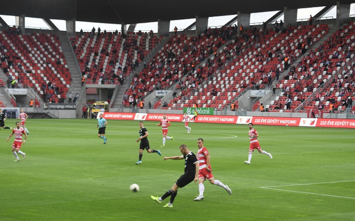 Players vie for the ball as supporters watch from the stands during the national championship's football match between DVTK and Mezokovesd in the DVTK stadium in Miskolc town, Hungary, on 30 May 2020. Picture: AFP.