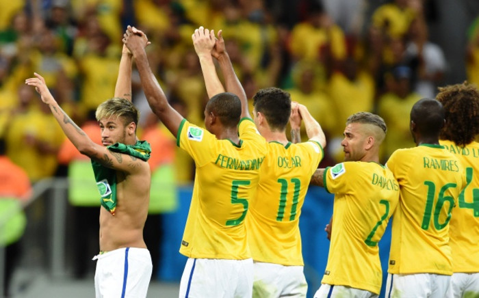 Brazil's forward Neymar (L) celebrates as he leaves the pitch with teammates at the end of a Group A football match between Cameroon and Brazil at the Mane Garrincha National Stadium in Brasilia during the 2014 Fifa World Cup on 23 June 2014. Picture: AFP.