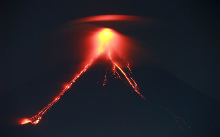 FILE: Lava cascades down the slopes of Mayon volcano as it erupts, as seen from Legazpi City in Albay province south of Manila on 15 January 2018. Picture: AFP.