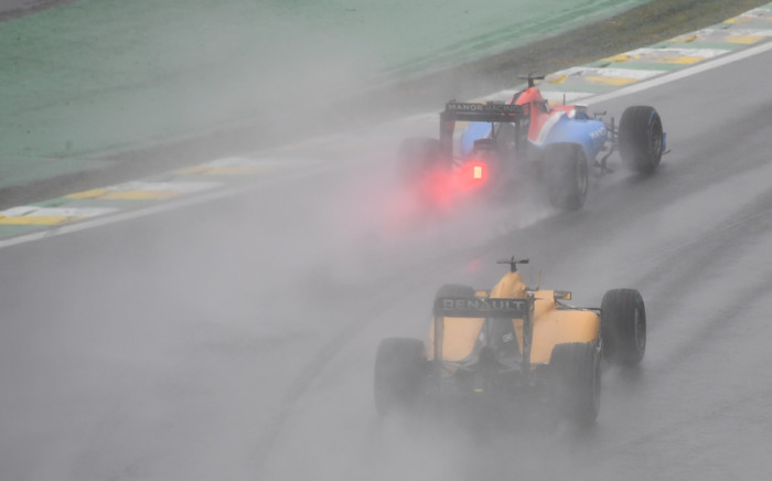 Manor's Racing's German driver Pascal Wehrlein (top) powers his car ahead of Renault Sport F1 Team's Danish driver Kevin Magnussen under the rain during the Brazilian Grand Prix at the Interlagos circuit in Sao Paulo, Brazil, on 13 November, 2016. Picture: AFP.