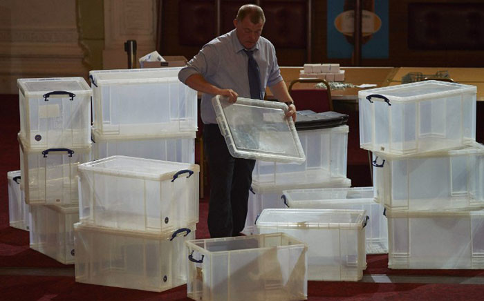 An election official stacks plastic boxes at a vote counting centre in Margate, southeast England, on May 7, 2015 in preparation for the arrival of the ballots during the UK general election. Picture: AFP