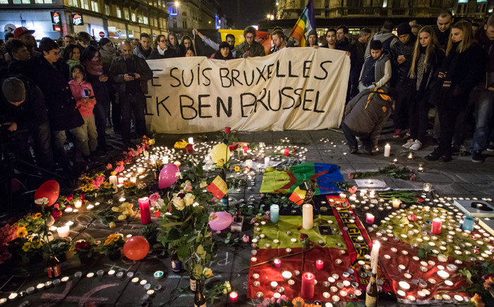 "People hold a banner reading in French and Flamish ""I AM BRUSSELS"" as they gather around floral tributes, candles, belgian flags and notes in front of the Bourse of Brussels on 22 March, 2016 in tribute to the victims of Brussels following triple bomb attacks in the Belgian capital that killed about 35 people and left more than 200 people wounded. Picture: AFP."