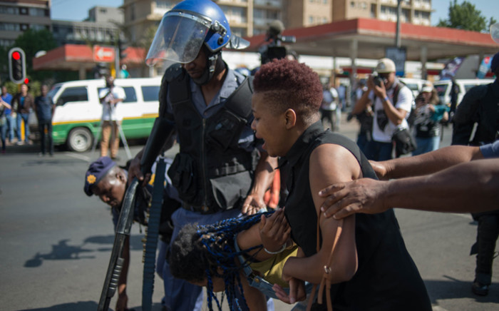 A student from the Wits University is detained by the police following clashes during the #FeesMustFall protest against the university fee increase on 4 October, 2016 in Johannesburg. Picture: AFP.