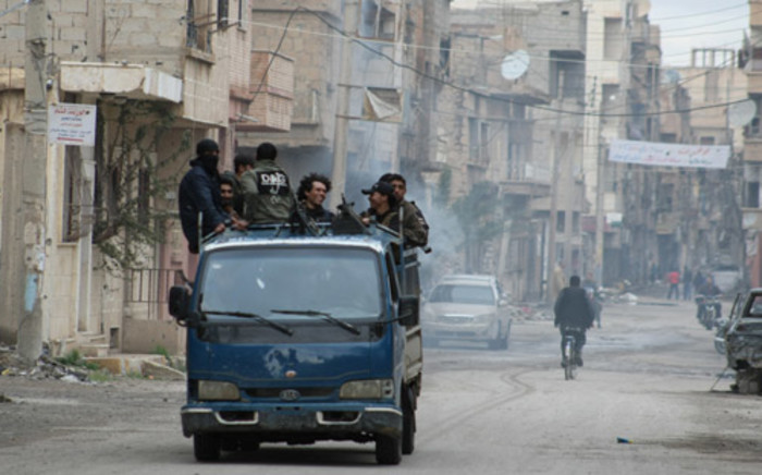 FILE: Rebels stand on the back of a pick-up truck driving through the eastern Syrian town of Deir Ezzor on 10 March, 2014. Picture: AFP.