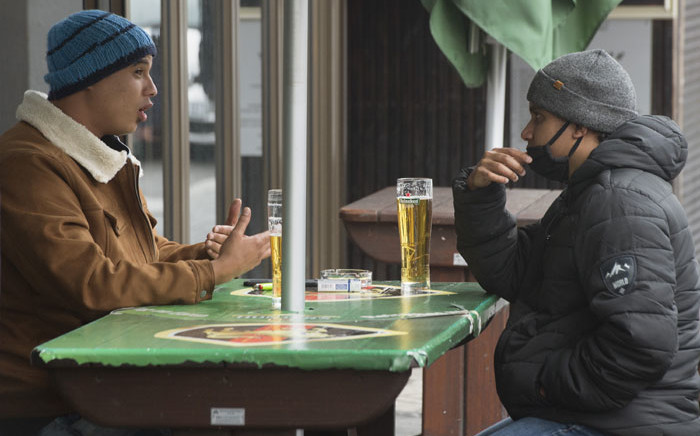 FILE: Two men enjoy some beers at a streetside bar in the city centre in Cape Town, on 18 August 2020 after South Africa moved to level 2 of the coronvirus lockdown. Picture: AFP