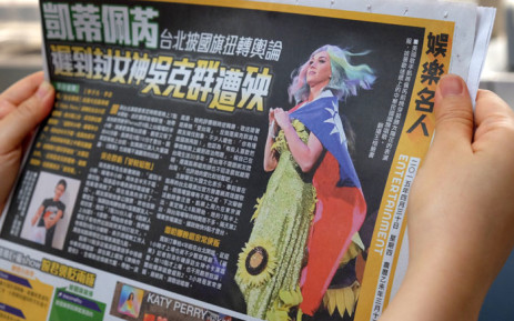 In this photo taken on 30 April 2015, a local resident reads a newspaper showing US singer Katy Perry wearing Taiwan's national flag in Taipei. Picture: AFP.